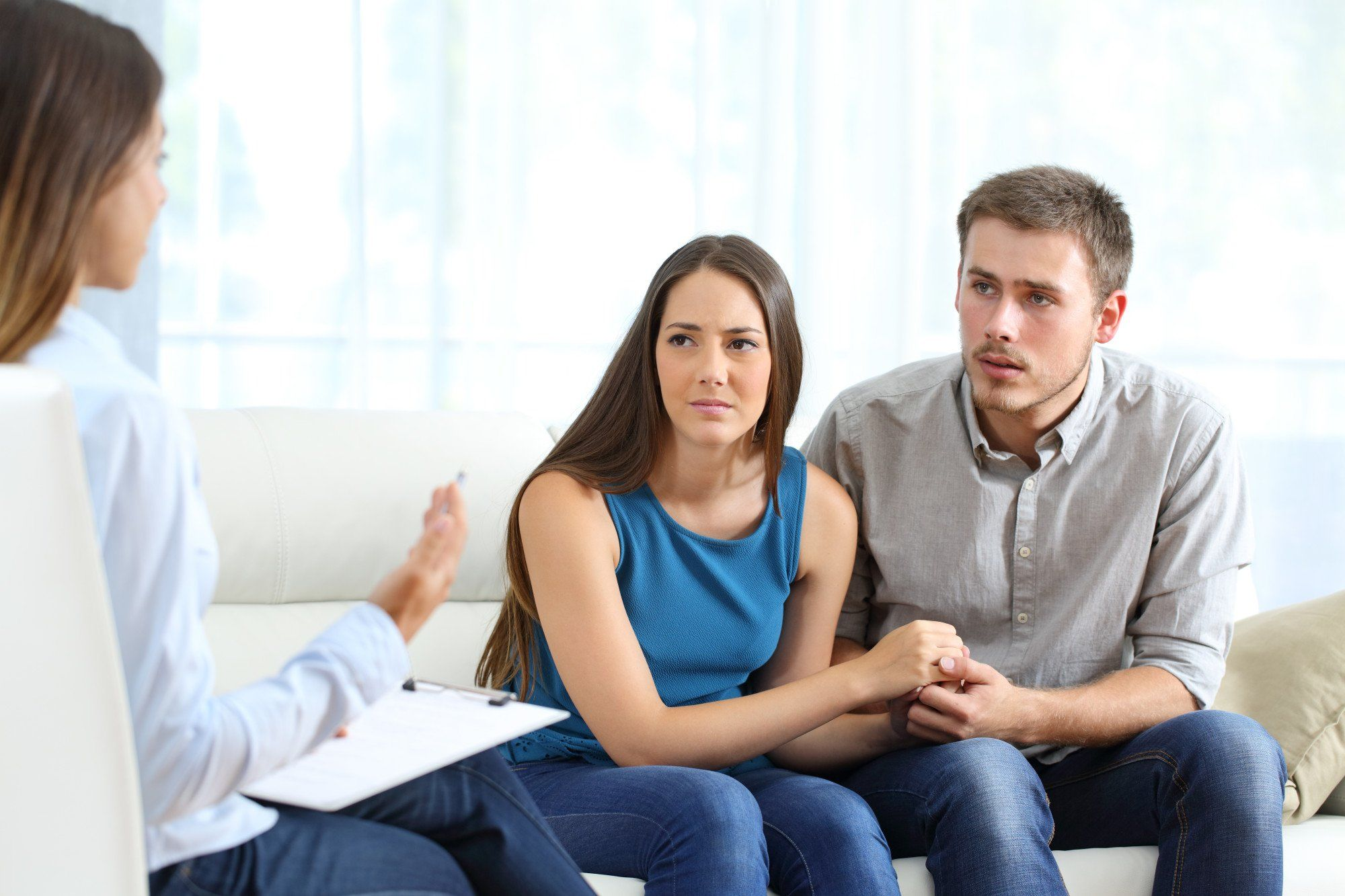 Worried couple listening to marriage counselor during a session